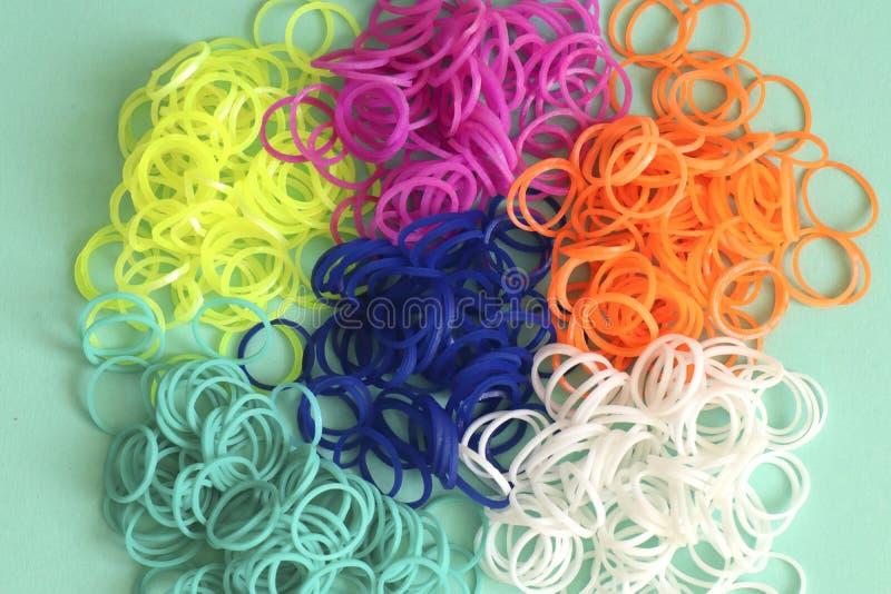 Pilha de el?sticos coloridos redondos pequenos para fazer os braceletes do tear do arco-?ris isolados no fundo da hortel? imagem de stock royalty free