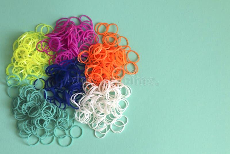 Pilha de el?sticos coloridos redondos pequenos para fazer os braceletes do tear do arco-?ris isolados no fundo da hortel? fotos de stock