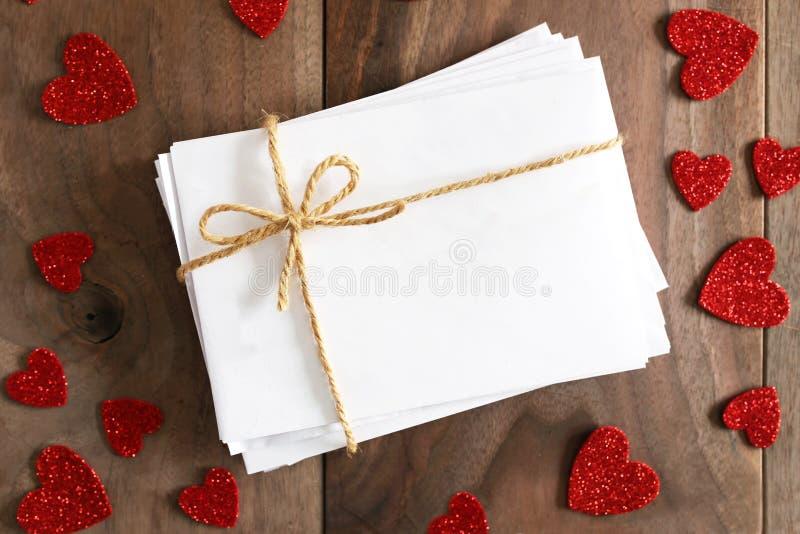 Pilha de envelopes amarrados com a curva da guita cercada pela forma do coração foto de stock