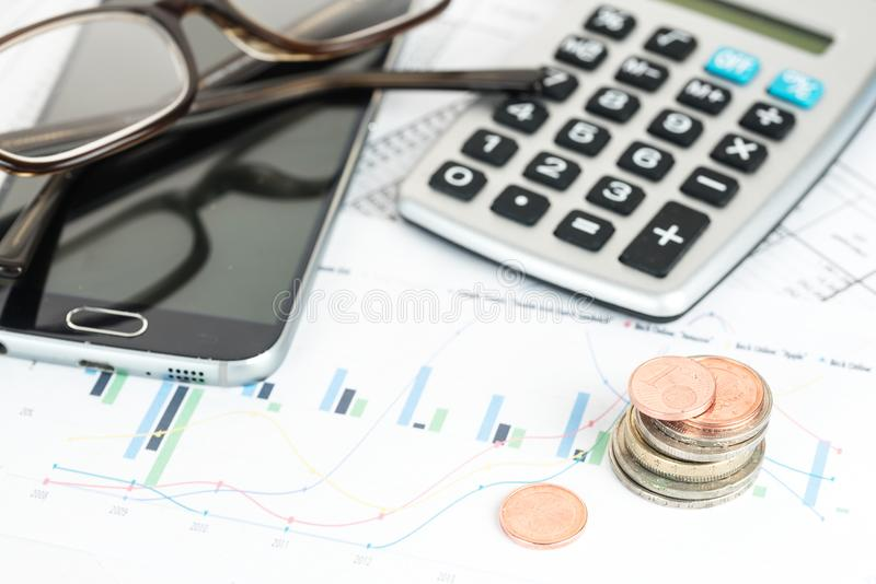Pilha de euro- moedas, calcualtor, telefone e vidros em um financia foto de stock royalty free