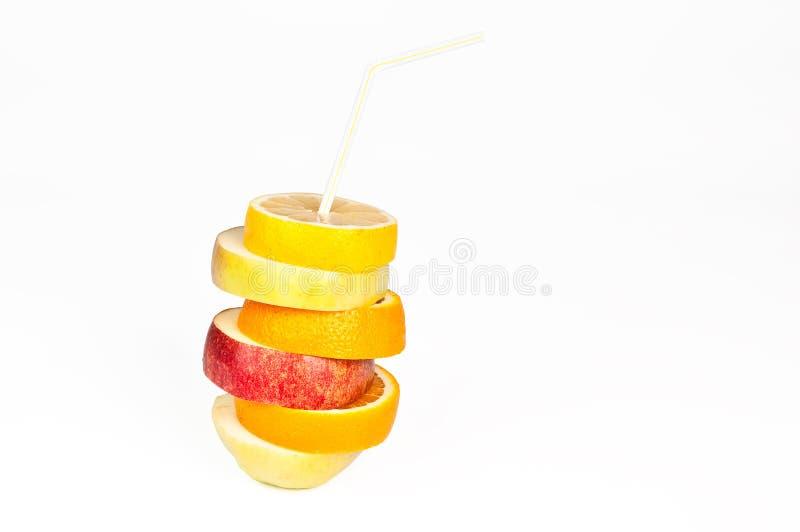 Pilha de fatias da laranja, do limão, da pera e da maçã com suco c da palha imagens de stock royalty free