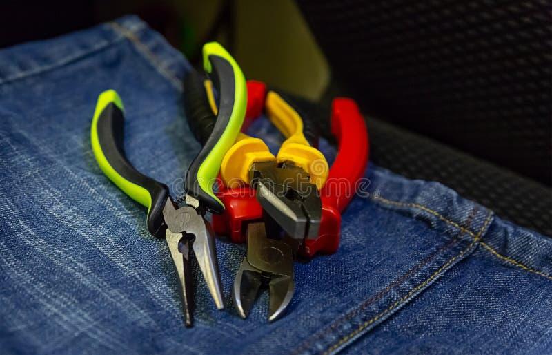 A pilha de ferramentas entrega alicates que o não-deslizamento colorido segura o trabalho com fundo industrial das ferramentas el imagens de stock royalty free