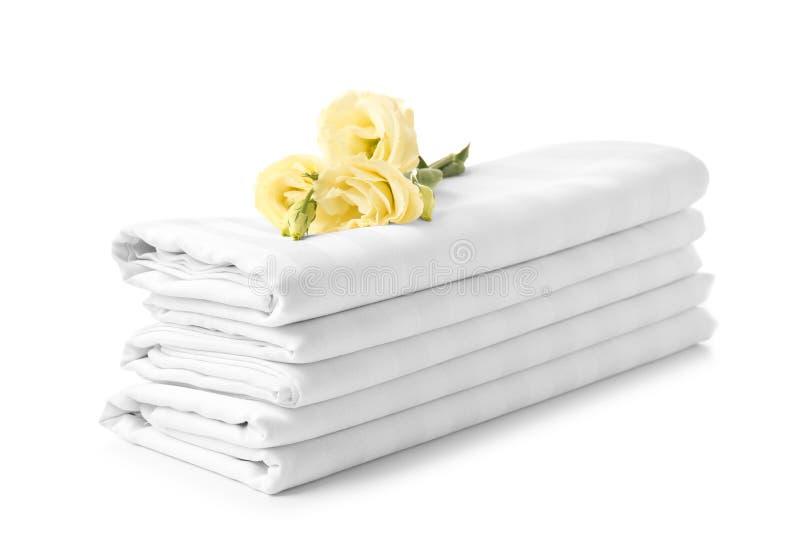 Pilha de folhas de cama limpas no fundo branco foto de stock royalty free