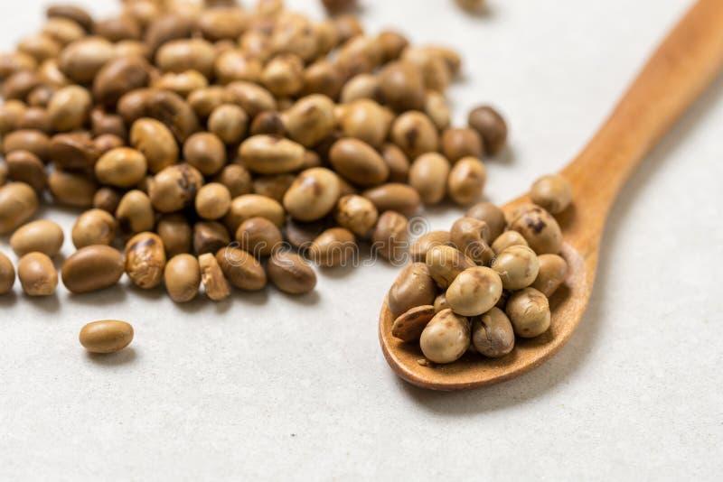 Pilha de grãos de soja com a colher de madeira na tabela de mármore branca do fundo foto de stock