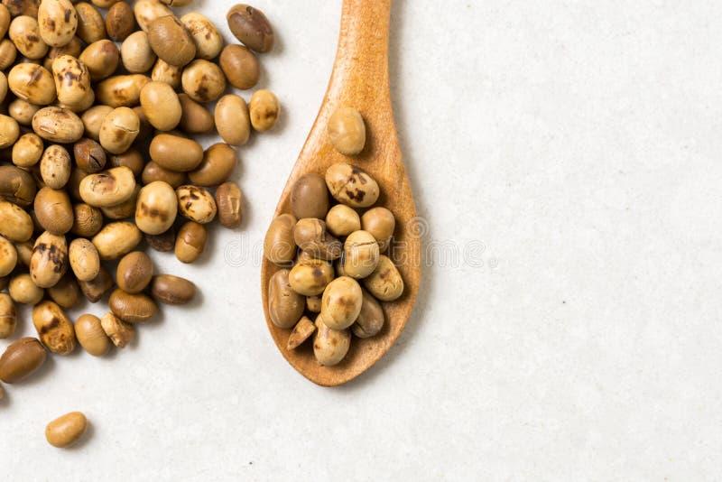 Pilha de grãos de soja com a colher de madeira na tabela de mármore branca do fundo fotografia de stock royalty free