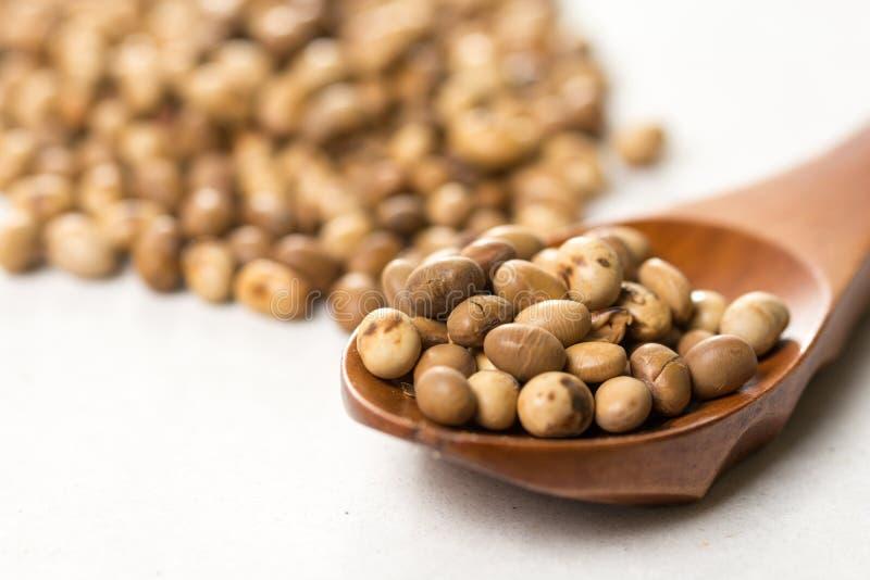 Pilha de grãos de soja com a colher de madeira na tabela de mármore branca do fundo imagem de stock