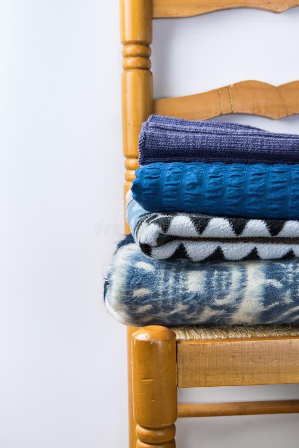 A pilha de home aquece coberturas azuis feitas malha das mantas do cinza bege áspero de Brown do fio de lãs no fundo branco da pa fotografia de stock