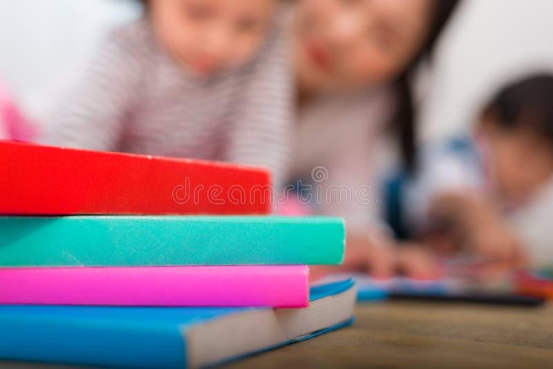 Pilha de livro colorido no assoalho com fundo da mulher obscura e das duas crianças Educa??o e conceito da aprendizagem tema do o fotos de stock