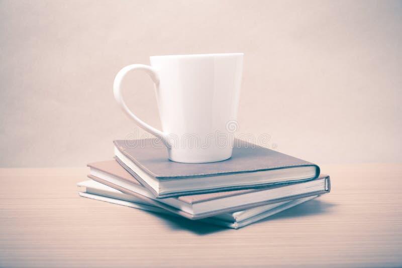 Pilha de livro com estilo do vintage da caneca de café foto de stock royalty free