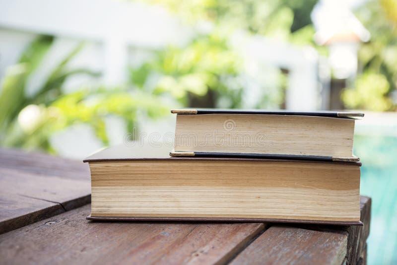Pilha de livro velho sobre o fundo borrado do jardim foto de stock royalty free