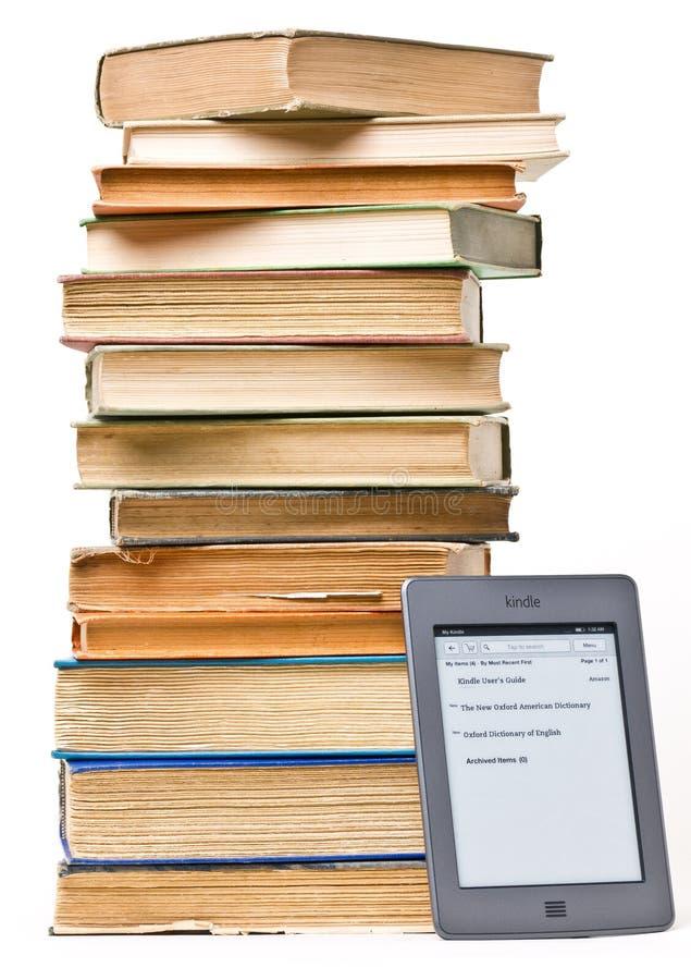 A pilha de livros ao lado de inflama o toque EReader imagem de stock