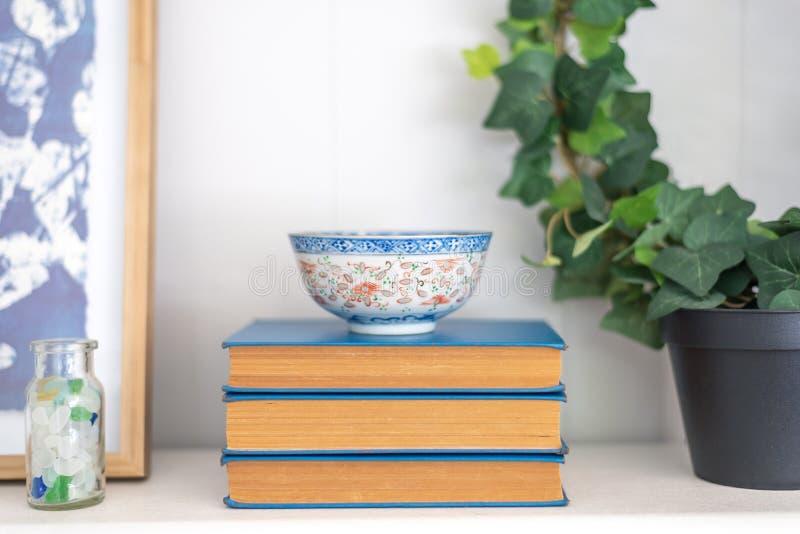 Pilha de livros azuis do vintage com a bacia de arroz oriental foto de stock