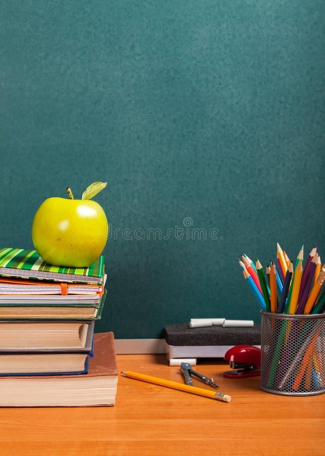 Pilha de livros coloridos e de maçã fresca foto de stock