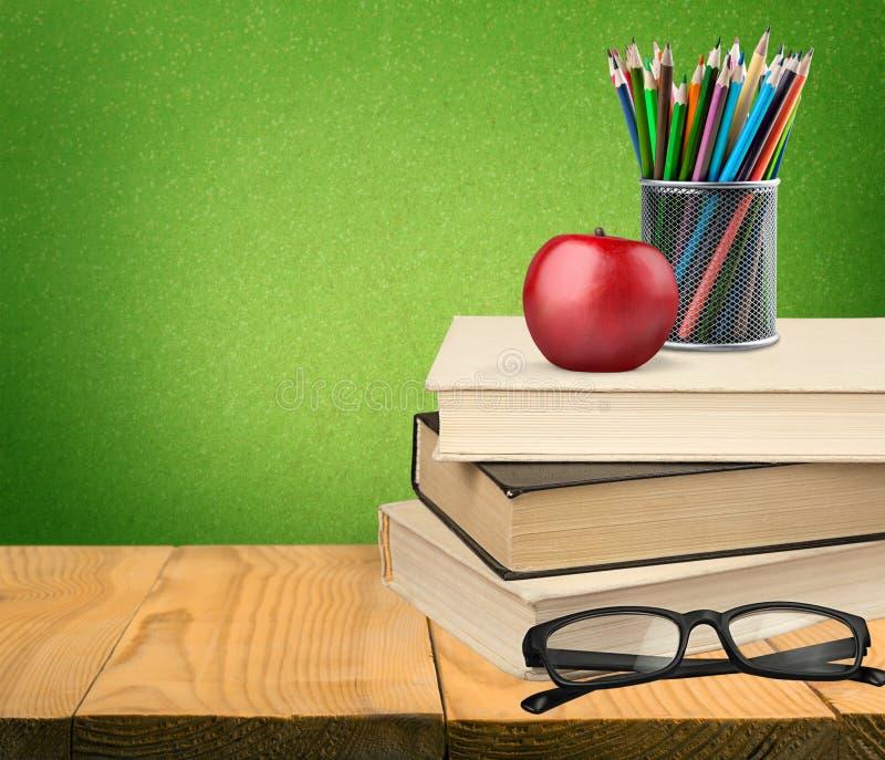 Pilha de livros coloridos e de maçã fresca imagem de stock
