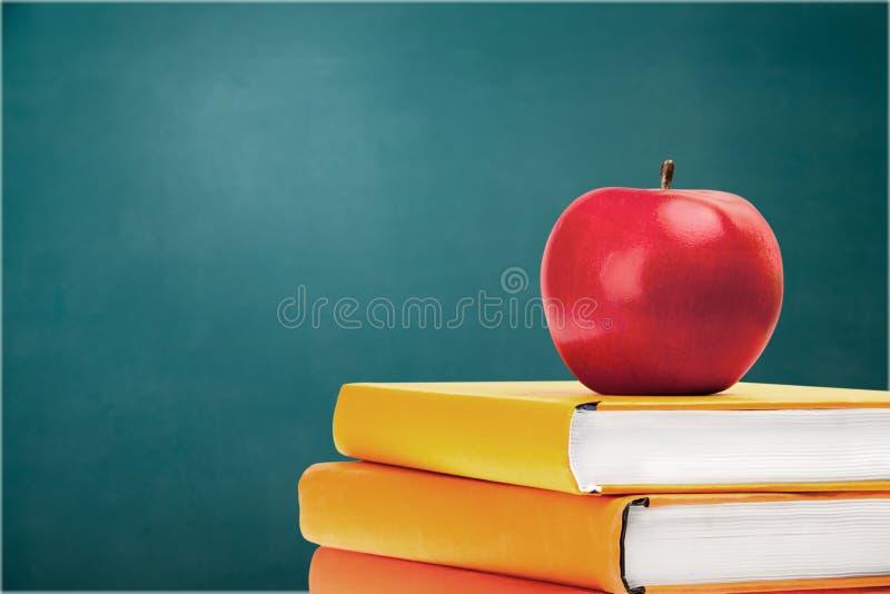 Pilha de livros coloridos e de maçã fresca imagens de stock royalty free