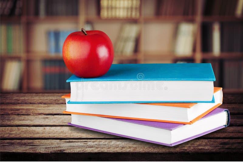 Pilha de livros coloridos e de maçã fresca fotografia de stock royalty free