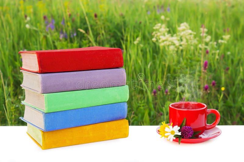 Pilha de livros coloridos na tabela e em um copo vermelho do chá quente em uns pires no fundo da natureza bonita fotografia de stock