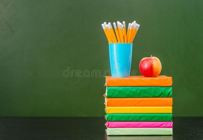 A pilha de livros com maçã e os lápis aproximam o quadro verde vazio foto de stock