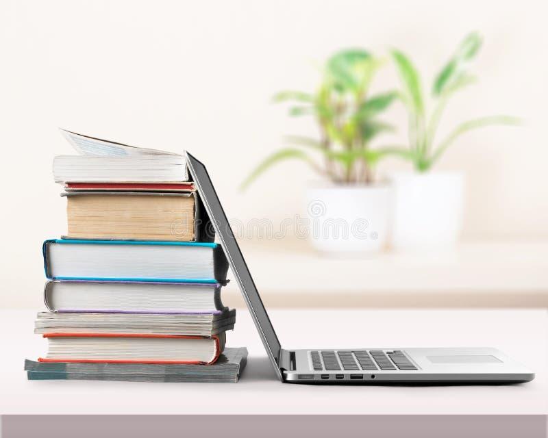 Pilha de livros com o portátil no fundo claro fotos de stock royalty free