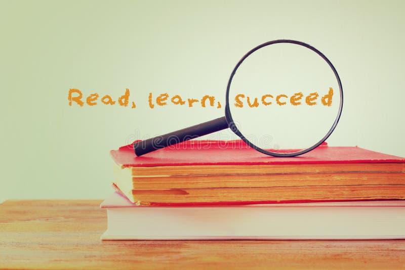A pilha de livros e a lupa com a frase aprendem que lido suceda Conceito da instrução fotografia de stock royalty free