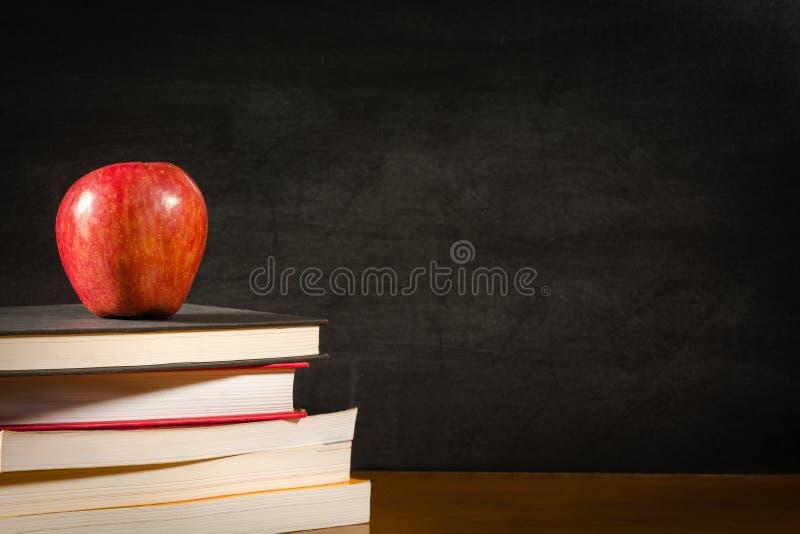 Pilha de livros e uma maçã vermelha em uma parte dianteira da mesa de um quadro-negro vazio foto de stock royalty free