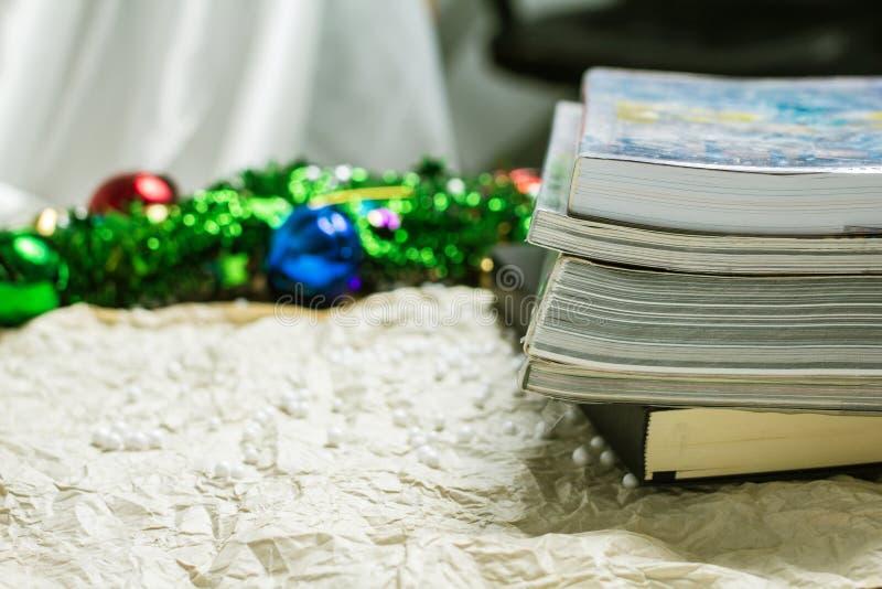 Pilha de livros em um crepe cinzento com um sino belamente colorido imagens de stock