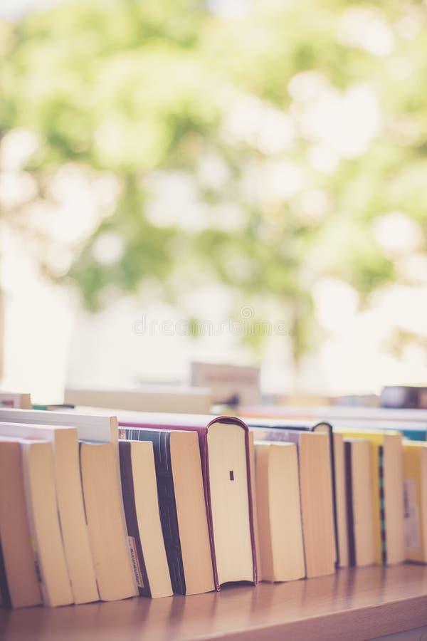 Pilha de livros em uma feira da ladra do livro da caridade, espaço do texto imagem de stock royalty free
