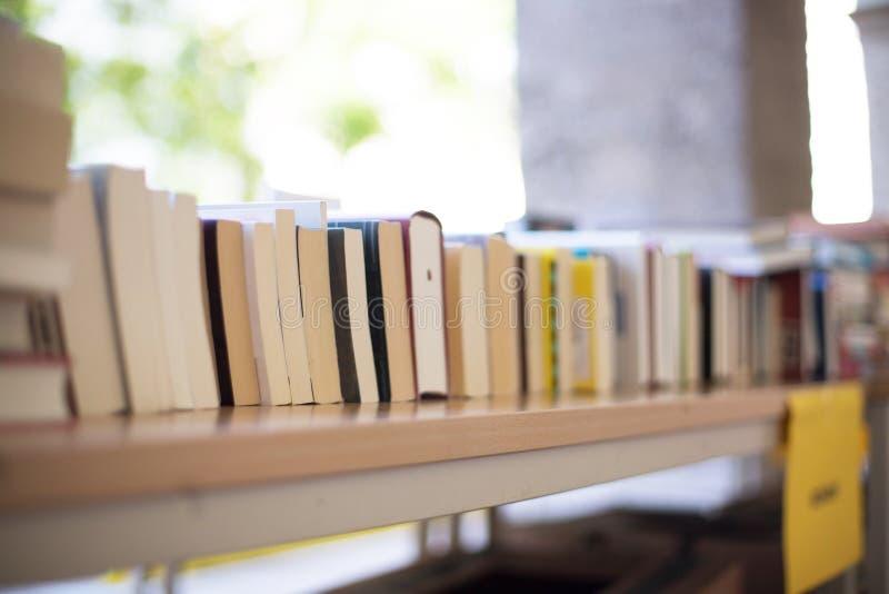 Pilha de livros em uma feira da ladra do livro da caridade, espaço do texto foto de stock royalty free