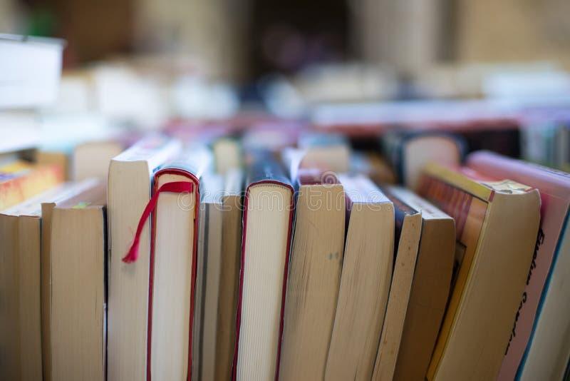 Pilha de livros em uma feira da ladra do livro da caridade, espaço do texto fotos de stock