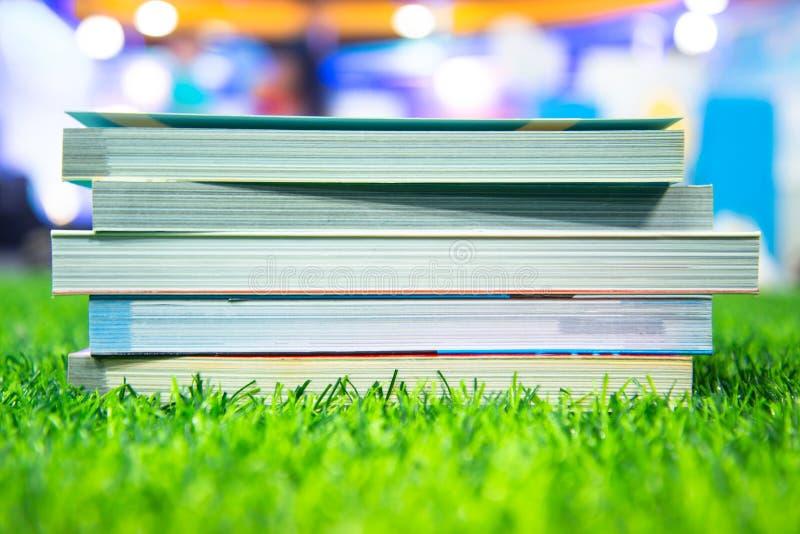 Pilha de livros no campo de grama verde fotos de stock