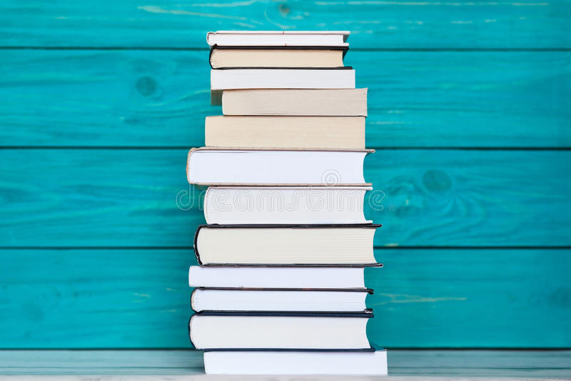 Pilha de livros no fundo de madeira de turquesa Concep da educação foto de stock