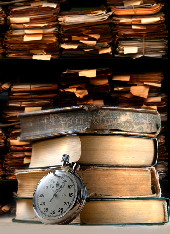 Pilha de livros velhos e de cronômetro fotografia de stock