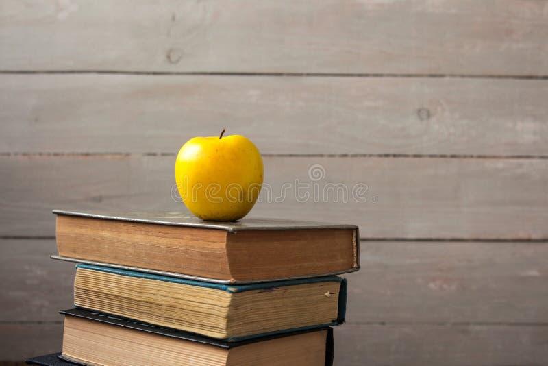 Pilha de livros velhos e de maçã no fundo de madeira foto de stock royalty free
