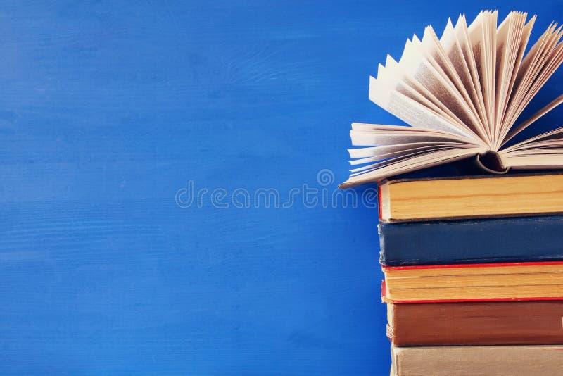 pilha de livros velhos na frente do fundo de madeira azul fotos de stock royalty free