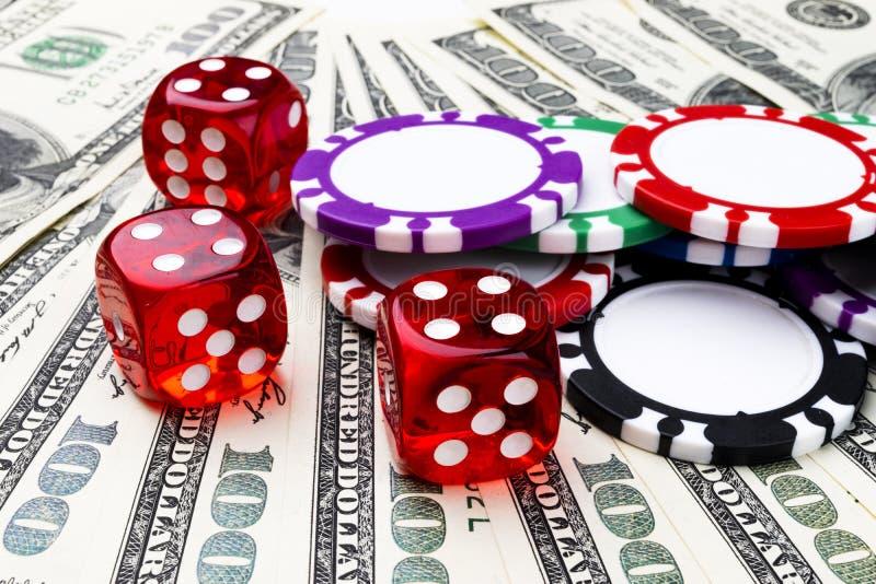 A pilha de microplaquetas de pôquer com dados rola no notas de dólar, dinheiro Tabela do pôquer no casino Conceito do jogo de pôq foto de stock