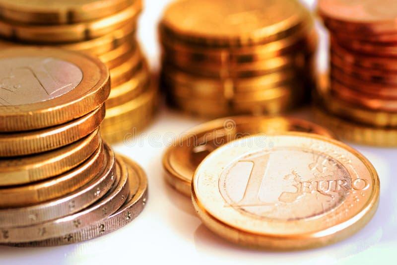 Pilha de moedas brancas e douradas brilhantes do valor diferente no fundo branco, finanças do Euro, investimento, estoque, econom fotos de stock royalty free