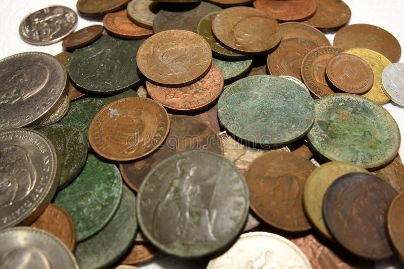 Pilha de moedas britânicas e europeias velhas do vintage foto de stock