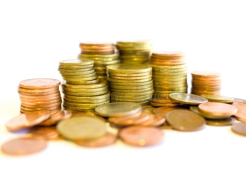 Pilha de moedas douradas e de cobre no fundo branco fotografia de stock royalty free