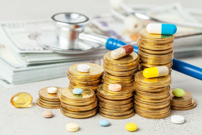Pilha de moedas e de comprimidos coloridos em um fundo cinzento com um estetoscópio e um dinheiro O conceito dos preços em subida fotografia de stock royalty free