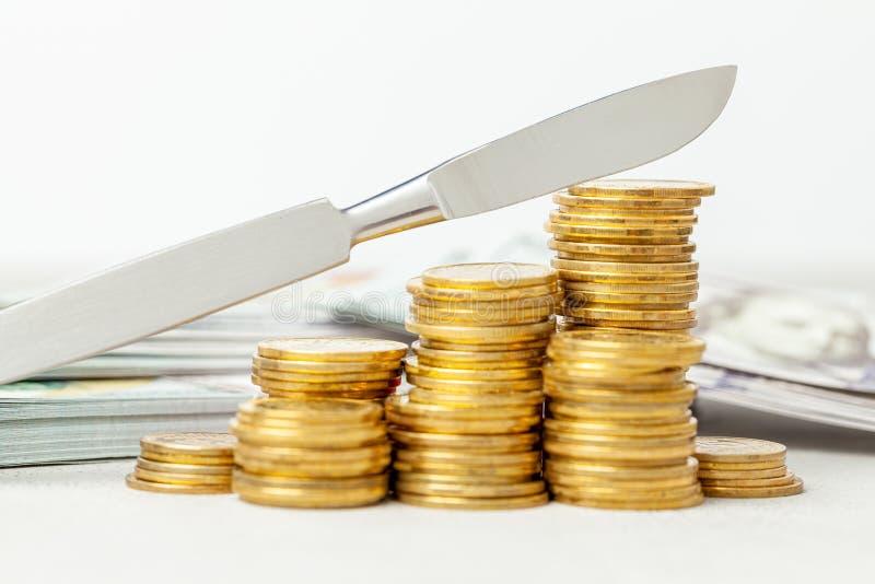 Pilha de moedas e de um escalpelo O conceito de serviços caros do cirurgião ou do seguro médico Fundo cinzento com dinheiro fotos de stock royalty free