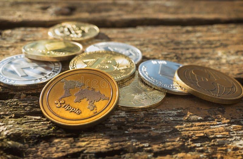 Pilha de muitas moedas criptos brilhantes na luz do dia na natureza no fundo de madeira da tabela Feche acima das moedas de prata fotos de stock