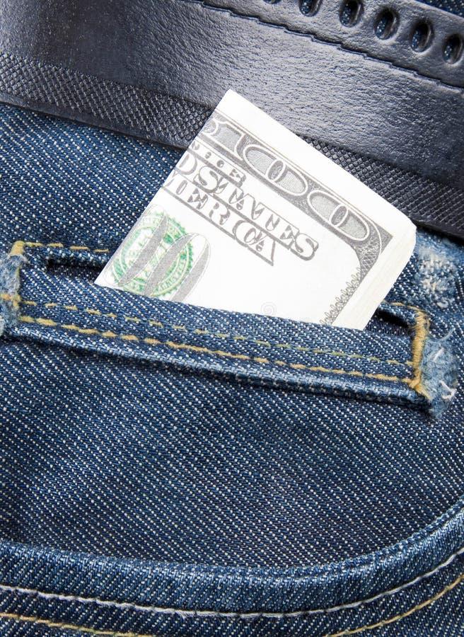 Pilha de notas de dólar no bolso das calças de brim fotografia de stock royalty free