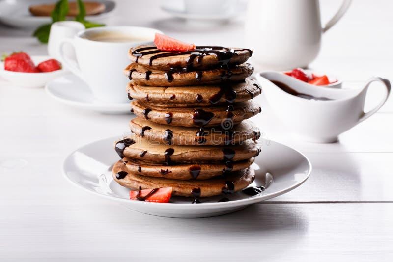 Pilha de panquecas do chocolate com cobertura e morangos do chocolate fotos de stock royalty free