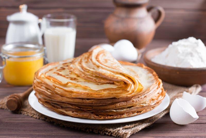 Pilha de panquecas finas do russo clássico bliny ou de crepes com mel em uma placa Tradicional para a semana Maslenit da panqueca fotografia de stock