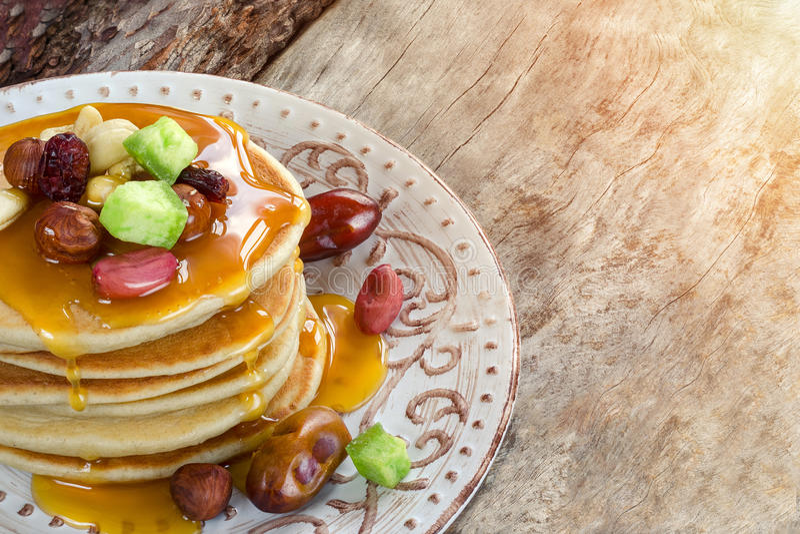 Pilha de panquecas quentes com porcas, frutos e xarope secados do caramelo imagem de stock royalty free