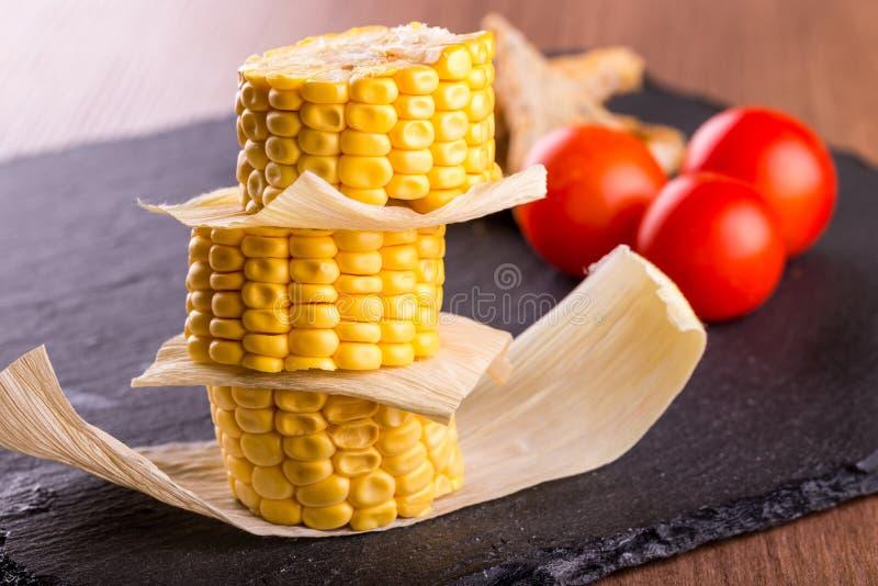 Pilha de parcelas do milho doce na placa da pedra da ardósia fotografia de stock