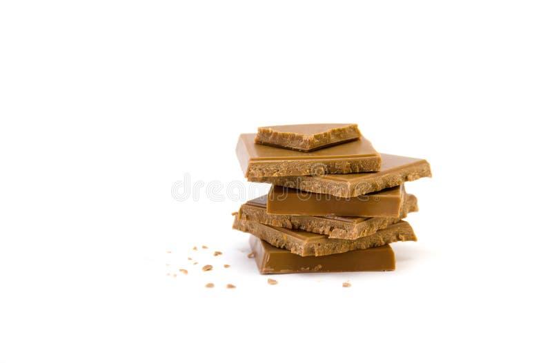 Pilha de partes e de migalhas do chocolate no foco seletivo do fundo branco imagem de stock royalty free