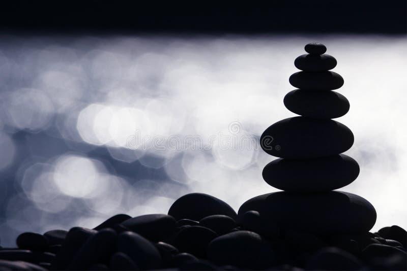 Pilha de pedra retroiluminada na praia fotos de stock royalty free