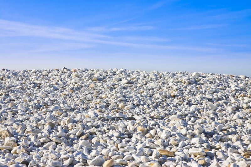 Pilha de pedras brancas arredondadas contra um céu azul imagens de stock royalty free