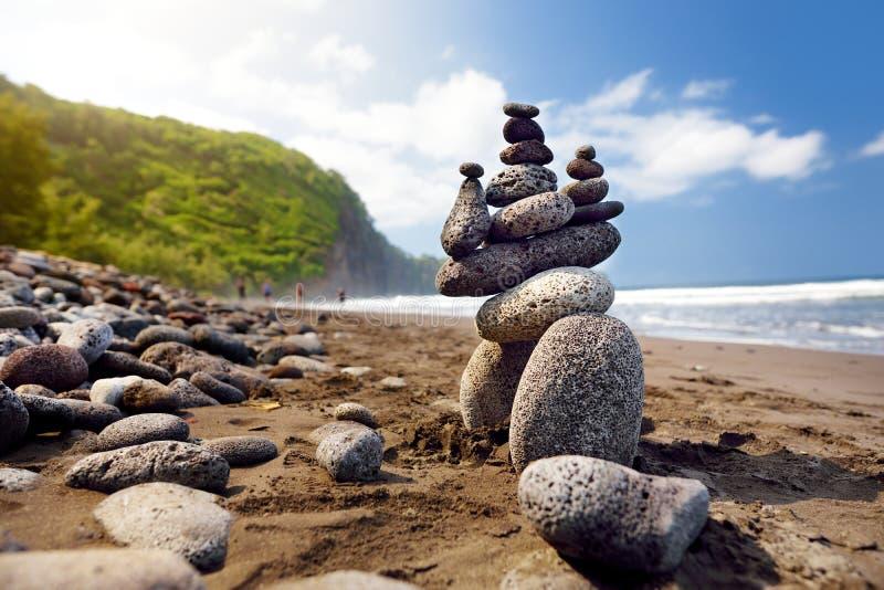 A pilha de pedras equilibrou na praia rochosa do vale de Pololu, ilha grande, Havaí fotos de stock
